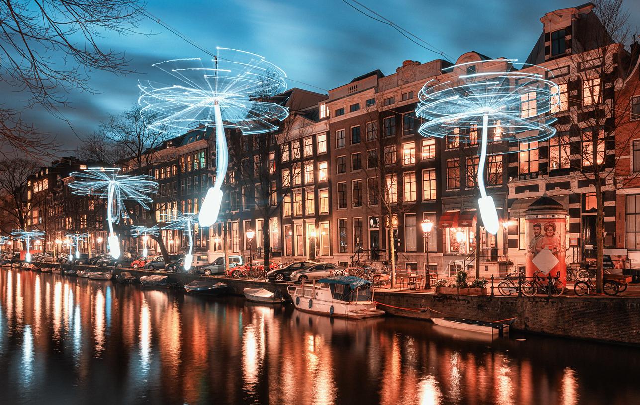 Széllel hajtott propellerek fehér fényt szórnak szét Amszterdamban a fényfesztiválon.