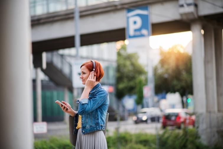 Városban sétáló nő headsettel a fején.
