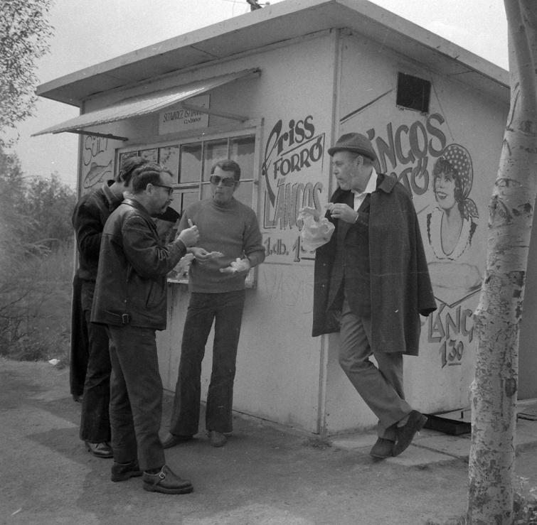 Várkonyi Zoltán lángost majszol egy velencei sütöde falának támaszkodva, 1972.