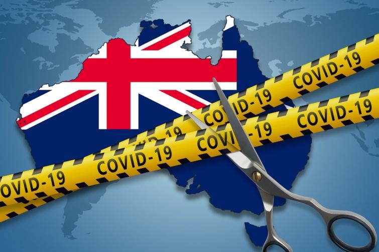 Nyitást szimbolizáló kép egy ollóval, Covid-19 feliratú sárga szalaggal és a háttérben Ausztráliával.