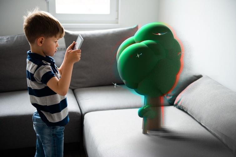 Egy kisfiú kiterjesztett valóságot használva játszik a tabletjével.