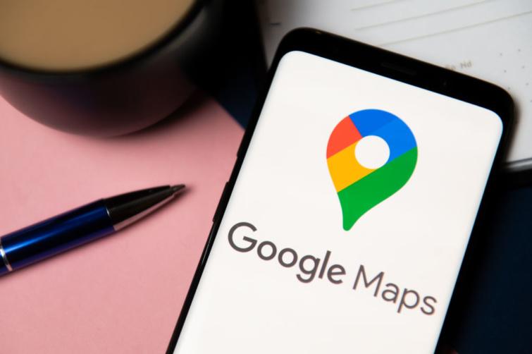 Google Maps alkalmazás a telefonon és toll egy asztalon.