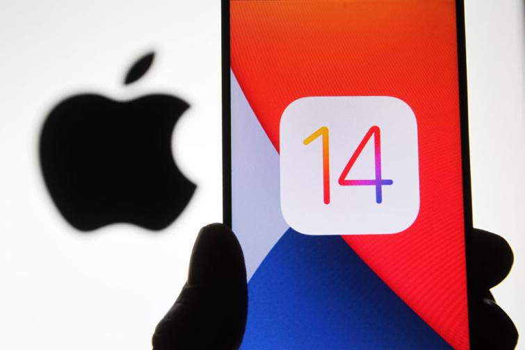 Az iOS új frissítésére utaló telefon, háttérben az Apple logóval.