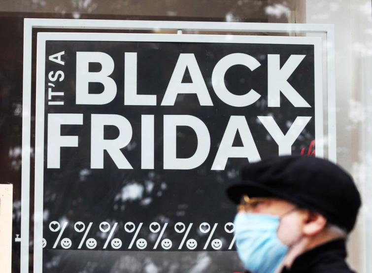 Maszkos férfi egy Black Friday hirdetés előtt.