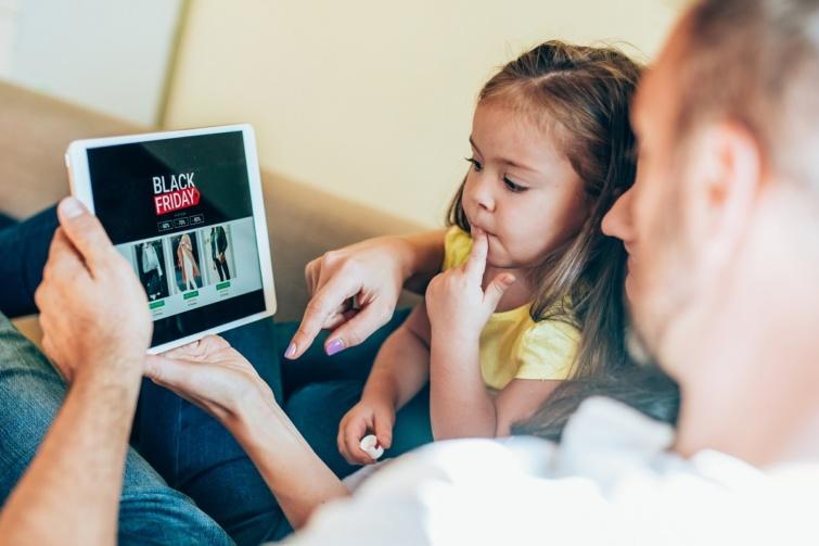 Apa és lánya a Black Friday kínálatát nézik egy tableten.